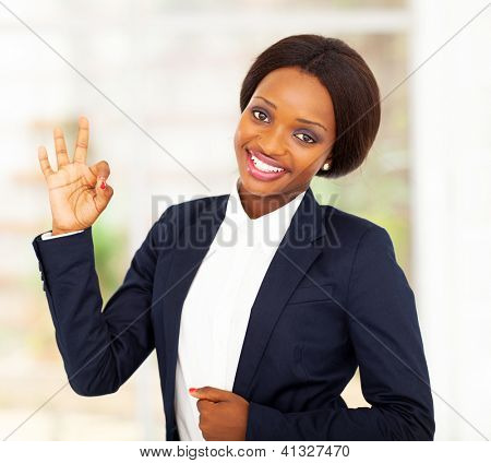 pretty african american businesswoman giving ok hand sign