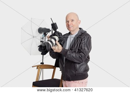 Happy middle age man with camera standing in photographer's studio