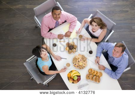 Four Businesspeople At Boardroom Table With Breakfast Smiling