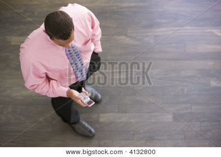 Businessman Standing Indoors Looking At Cellular Phone