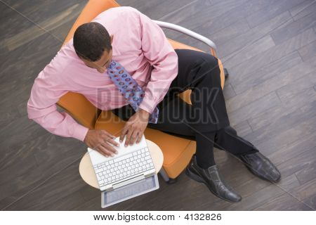 Businessman Sitting Indoors With Laptop