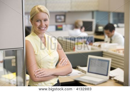 Businesswoman Standing In Cubicle Smiling