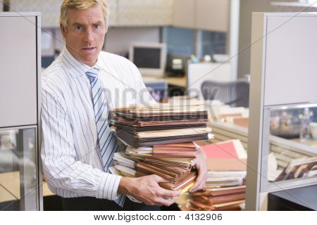 Businessman Standing In Cubicle Holding Stacks Of Files
