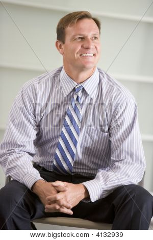 Businessman Sitting Indoors Smiling