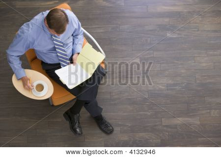 Businessman Sitting Indoors With Coffee And Folder