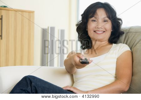 Woman Sitting In Living Room Holding Remote Control Smiling