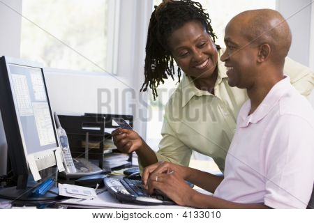 Couples In Home Office With Credit Card Using Computer And Smiling