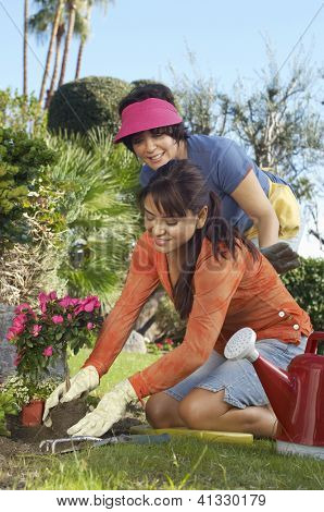 Happy daughter planting flower plant with mother standing in the background at garden