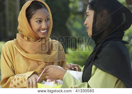 Two happy Asian women looking at each other while holding shopping bags