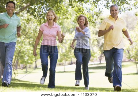 Two Couples Running Outdoors Smiling