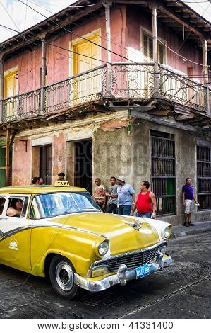 SANTIAGO DE CUBA,CUBA-JANUARY 11:Old Buick next to crumbling buildings January 11,2013 in Santiago de Cuba.Thousands of these classic cars are used as taxis and private vehicles across the country