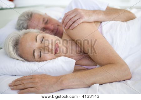 Couples Lying In Bed Together Sleeping