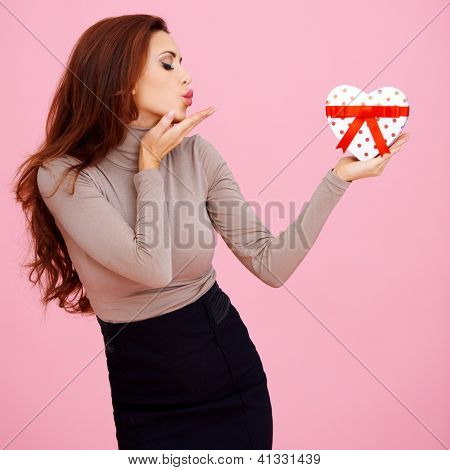Beautiful woman holding a heart shaped Valentine gift in her hand blowing a romantic kiss on a pink studio background