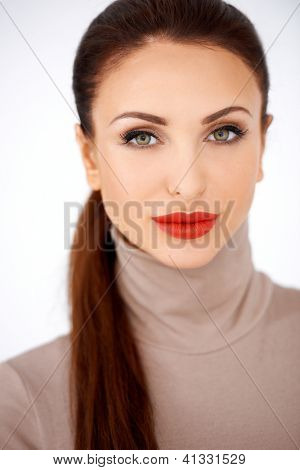 Glamorous elegant woman in red lipstick wearing a stylish polo neck top, head and shoulders frontal portrait isolated on white