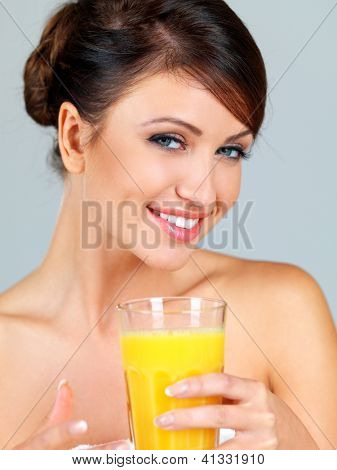 Smiling beautiful woman with bare shoulders drinking a large glass of freshly squeezed orange juice