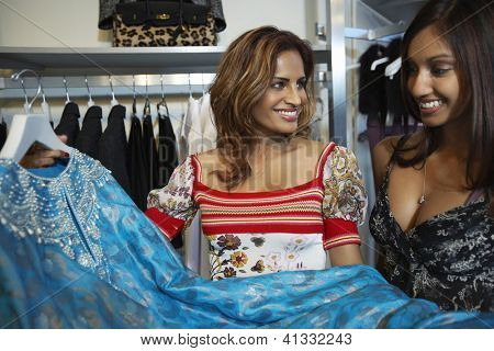 Two happy women selecting a dress while shopping for clothes at shop