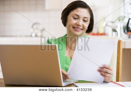 Woman In Kitchen With Laptop And Paperwork Smiling