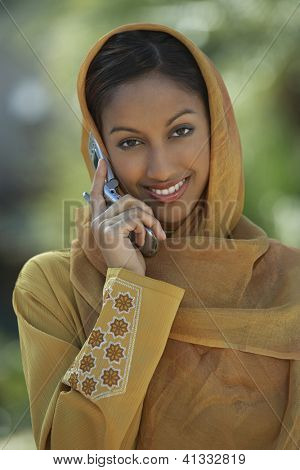 Portrait of an Indian woman in traditional dress using cell phone