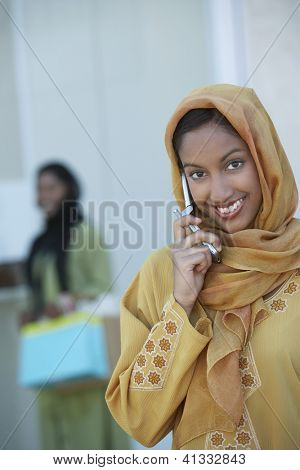 Portrait of a happy Indian female on a call with woman in the background