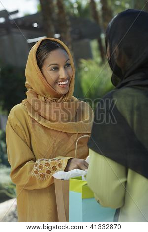 Happy Indian woman looking at friend while holding shopping bag