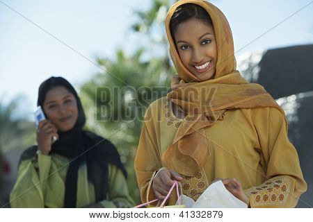 Portrait of happy Indian woman holding shopping bags with female friend on a call in the background