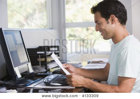 Man In Home Office Using Computer Holding Paperwork And Smiling