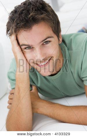 Hombre acostado en la sala de estar sonriendo