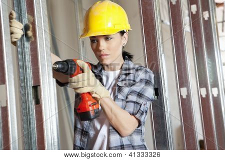 Young female contractor drilling at construction site