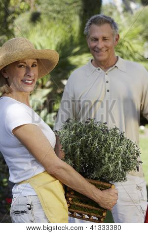 Portrait of a senior woman holding plant with man standing in the background