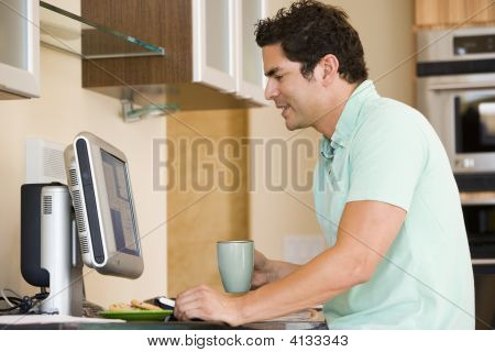Man In Kitchen With Coffee Using Computer And Smiling