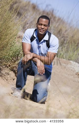 Man Crouching On Path To Beach Smiling