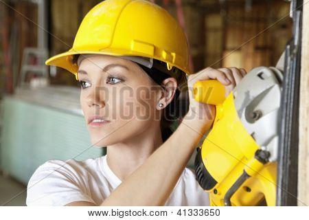Construção feminino trabalhador cortar madeira com um poder viu enquanto olhando para longe