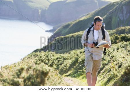 Man Walking On Cliffside Path Looking At Map