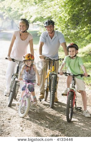 Families Sitting On Bikes On Path Smiling