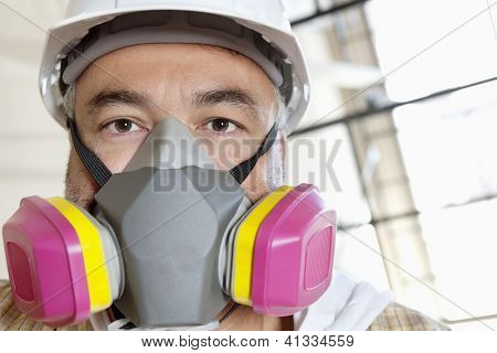 Portrait of male worker wearing dust mask at construction site