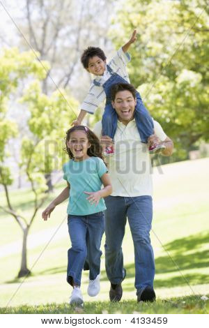 Man With Two Young Children Running Outdoors Smiling