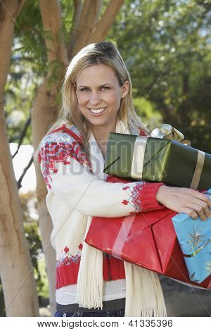 Portrait of a happy young woman carrying gift boxes