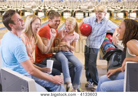 Families In Bowling Alley With Two Friends Cheering And Smiling