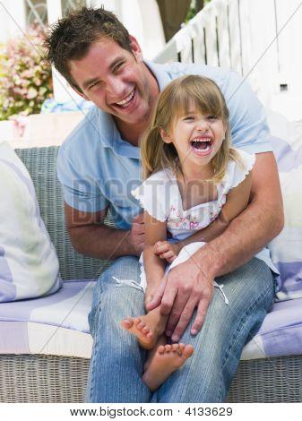 Hombre y joven, sentado en el Patio riendo