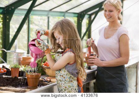 junge Mädchen im Gewächshaus Bewässerung von Pflanzen mit Woman holding Pot lächelnd