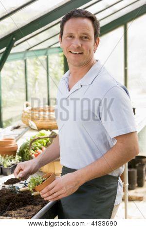 Man In Greenhouse Putting Soil In Pot