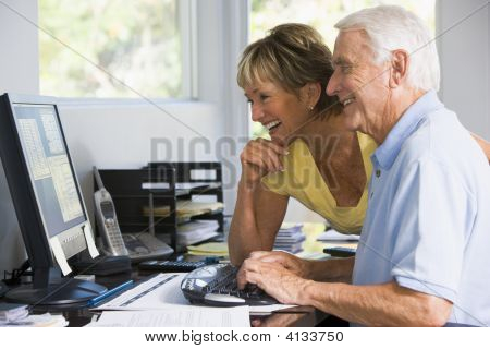 Couples In Home Office With Computer And Paperwork Smiling