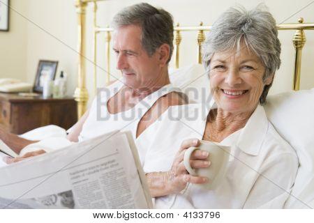 Parejas en dormitorio con café y periódicos sonriendo