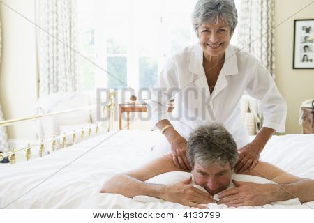 Woman Giving Man Massage In Bedroom Smiling