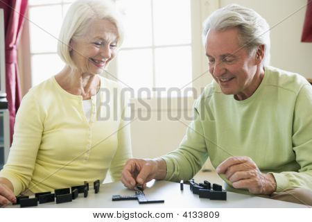 Couples Playing Dominos In Living Room Smiling