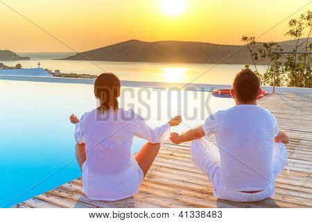 Couple meditating together at sunrise