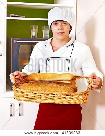 Male chef baking baguette bread.
