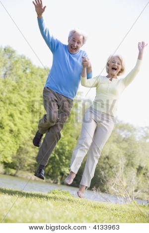 Couples Jumping Outdoors At Park By Lake Smiling