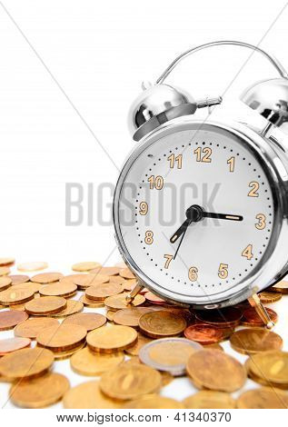 Alarm clock on gold coins.