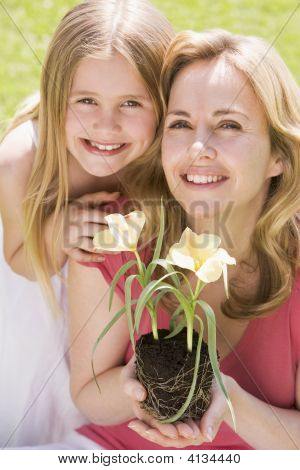 Mother And Daughter Outdoors Holding Flower Smiling